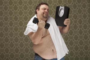 Hombre con sobrepeso sosteniendo escalas trabajando duro para perder peso