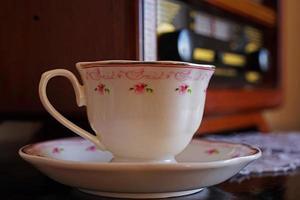 Bodegón con vieja taza de café y radio nostálgica foto