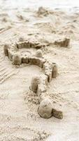 Sandcastle and wall barrier on sandy beach during summer day