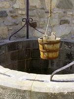 Wishing well with a bucket ready to be lowered by a rope photo