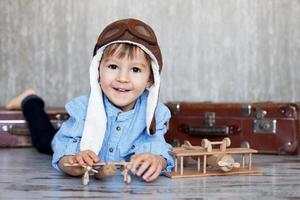 Little boy, playing with wooden planes, indoor, suitcases behind him