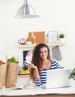 sonriente mujer joven con una taza de café y una computadora portátil en el foto