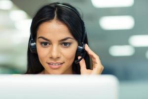 Businesswoman working on laptop with headphones photo