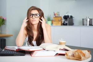 Happy young woman studying in kitchen photo