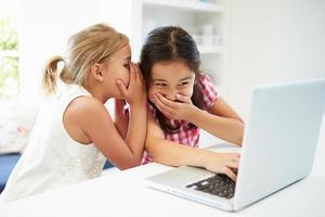 Dos chicas jóvenes usando una computadora portátil en casa y susurrando foto