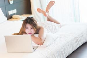 Beautiful young woman in bathrobe working with laptop on bed