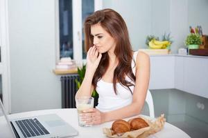mujer joven sonriente que usa la computadora portátil foto