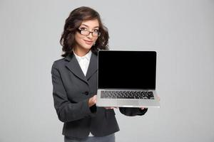 Confident pretty female showing blank laptop computer screen