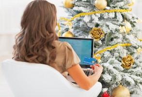 Mujer con tarjeta de crédito y portátil cerca de árbol de Navidad