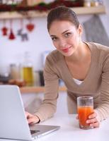 Woman using a laptop while drinking juice in her kitchen