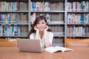 Hermosa estudiante asiática usando laptop para estudiar en la biblioteca