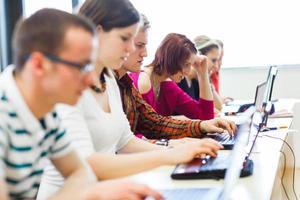 estudiantes universitarios sentados en un salón de clases usando computadoras portátiles
