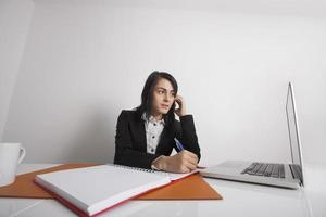 Businesswomen using cell phone while writing notes from laptop photo