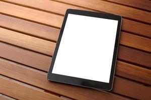Digital tablet computer on wooden desk.