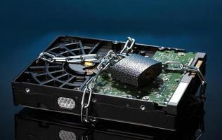 Hard disk drive on chain on dark blue background