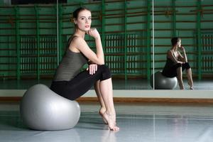 Woman sitting with exercise ball photo