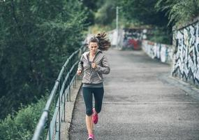 fitness young woman jogging in the city park photo