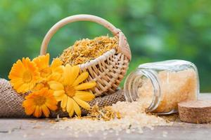 Marigold flowers, basket with dried plants and sea salt
