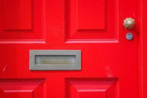 puerta roja con buzón de latón