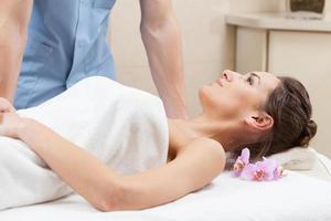 mujer envuelta en una toalla blanca acostada en la mesa de masaje foto