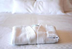 hotel bed with white bathrobe