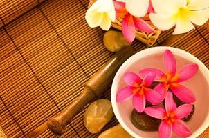 Tropical spa with Frangipani flowers on water.