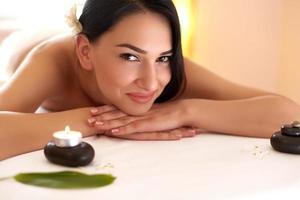 masaje spa hermosa morena recibe tratamiento de spa en el salón. foto