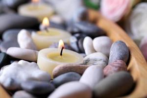 Tazón de madera con piedras de spa y velas en la mesa de madera