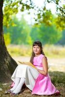 Beautiful teenage girl reads the book under huge oak tree