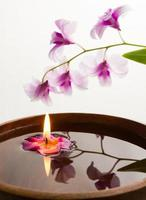 spa concept with candle in wooden bowl.