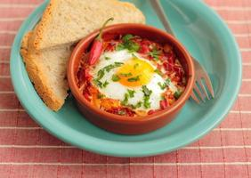 Eggs poached in tomato sauce photo