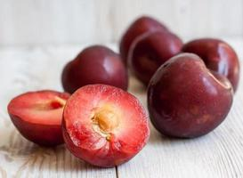 Ripe plums on a white wooden background