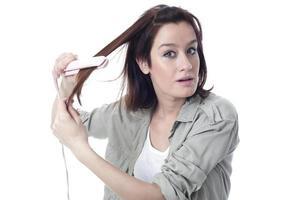Caucasian girl using hair iron