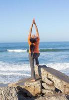 mujer caucásica practicando yoga en la orilla del mar foto