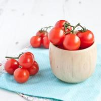 Tomatoes in wooden bowl on the whte table photo
