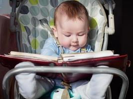 Small caucasian baby boy sitting in chear with notepad