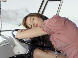 mujer descansando sobre el volante de la furgoneta