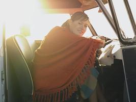 mujer feliz en el asiento del conductor de la furgoneta