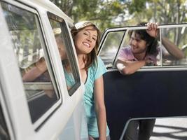 Pareja asomada de autocaravana durante el viaje por carretera