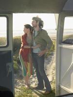 Pareja abrazándose en la vista de la playa a través de la puerta de la autocaravana