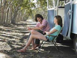 pareja sentada en hamacas al lado de autocaravana