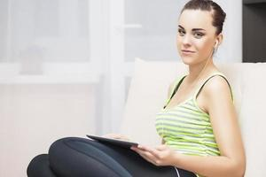 Caucasian Female With Headphones Using Tablet at Home Environment