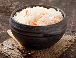 Sauerkraut with carrot in wooden bowl photo