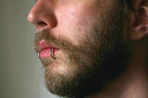 Cerca de la cara del hombre con piercings en los labios foto