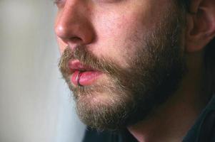 Cerca de la cara del hombre con piercing en los labios foto