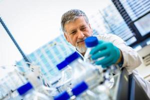 Investigador senior masculino realizando investigación científica en un laboratorio
