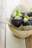 Mangosteen in wood bowl on table