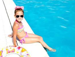 menina sorridente, sentado perto da piscina