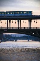 Bir Hakeim Bridge with metro and silhouette photo