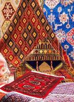 Alfombras orientales en el mercado. Imagen de la mezquita en una de las alfombras.
